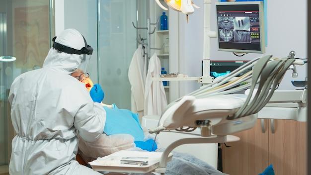 Odontotecnico in equipaggiamento protettivo che accende la lampada per esaminare il paziente durante l'epidemia di covid-19. equipe medica che parla con una donna che indossa visiera, tuta, maschera e guanti
