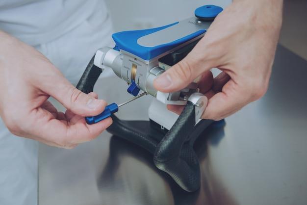 Odontotecnico che lavora con l'articolatore in laboratorio odontotecnico