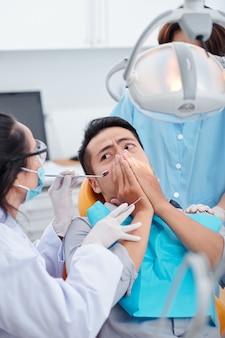Dentista che chiede al paziente spaventato di calmarsi e di smettere di coprirsi la bocca in modo da potergli controllare i denti