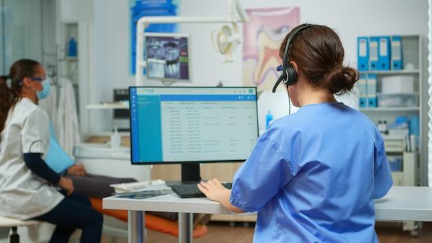 Assistente dentista che fissa appuntamenti utilizzando l'auricolare seduto di fronte al computer mentre il medico sta lavorando con il paziente in background esaminando il problema dei denti. infermiera che prende appunti in studio stomatologico