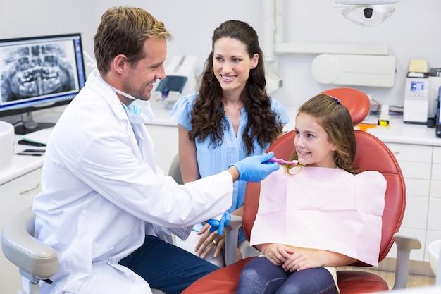 Dentista che assiste il giovane paziente a lavarsi i denti