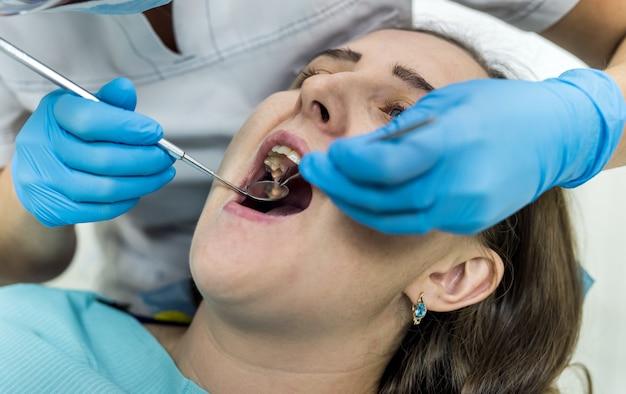 Dentista che controlla i denti del paziente con lo specchio in odontoiatria
