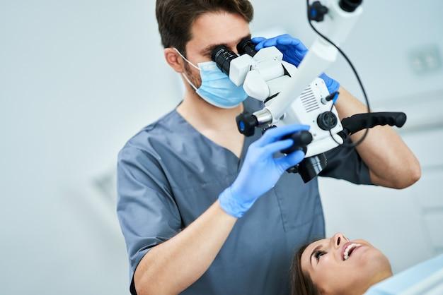 Dentista che controlla i denti del paziente con il microscopio presso l'ufficio chirurgico