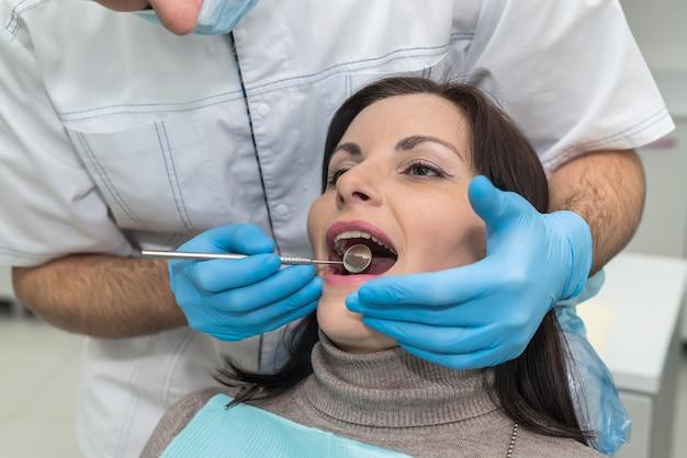 Dentista che controlla i denti della donna con lo specchio durante la visita