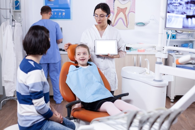 Dentista in clinica con chiave di crominanza sul display tablet pc consulenza bambino con dente difettoso. stomatolog che spiega la prevenzione dei denti alla madre e al bambino che tengono tablet pc con copia spazio disponibile.