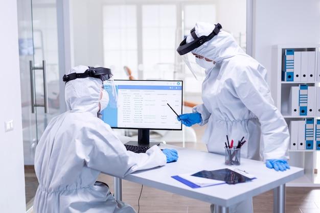 Colleghi dentisti vestiti con tuta dpi durante il covid 19 usando il computer. squadra di medicina che indossa indumenti di protezione contro la pandemia di coronavirus nella ricezione dentale come precauzione di sicurezza.
