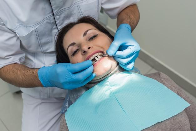 Dentista che confronta il colore dei denti del paziente con il campionatore