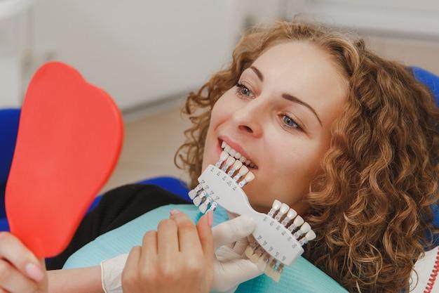 Il dentista confronta il colore dei denti del paziente con i campioni per il trattamento di sbiancamento