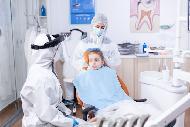 Dentista in tuta che parla con il bambino prima dell'esame odontoiatrico con maschera facciale. stomatologo durante il covid19 che indossa una tuta in dpi facendo la procedura dei denti del bambino seduto sulla sedia.