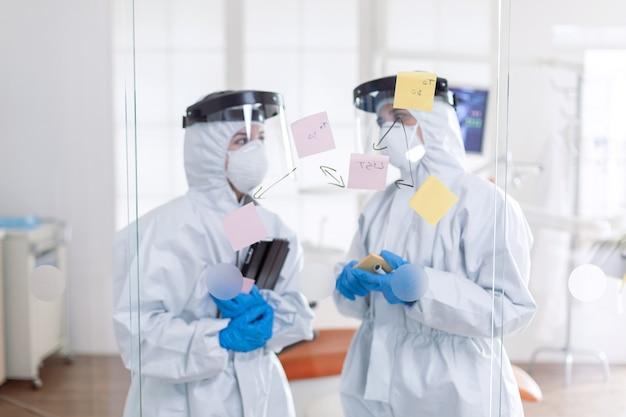 Colleghi dentisti che parlano di problemi ai denti che indossano la tuta da pipì come precauzione di sicurezza per covid-19. equipe medica nell'ufficio di stomatologia che indossa una tuta in studio dentistico che scrive idee su note adesive.