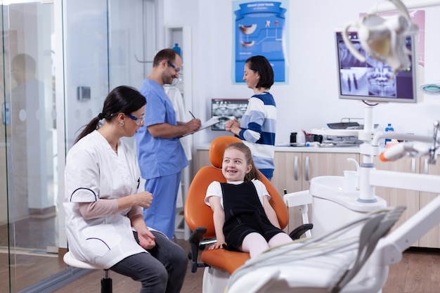 Dentista in studio dentistico facendo ridere bambina bambino con sua madre durante il check-up dei denti con stomatolog seduto sulla sedia.