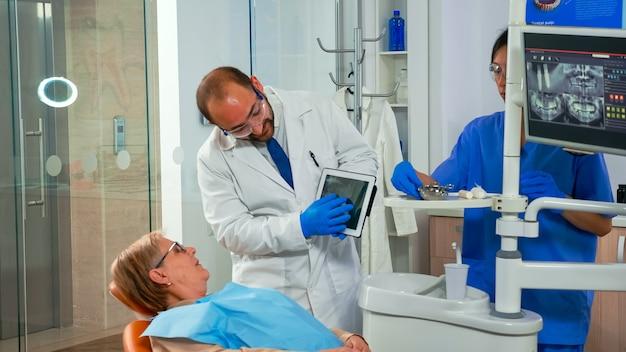 Dentista in studio dentistico che parla con una paziente e si prepara per il trattamento, esaminando l'immagine a raggi x sul tablet. medico che mostra all'anziana radiografia dentale gadget moderno in clinica stomatologica.