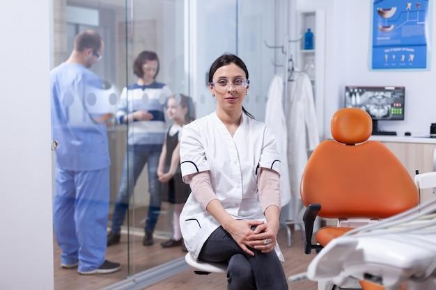 Dentista nell'ufficio di odontoiatria seduto sulla sedia mentre l'assistente sta parlando con la madre e la sua bambina. stomatolog nella clinica dei denti professioanl sorridente indossando l'uniforme che guarda l'obbiettivo.