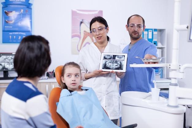 Dentista che discute sulla prevenzione della cavità con il genitore della bambina stomatologo che spiega la diagnosi dei denti alla madre del bambino nella clinica sanitaria che tiene i raggi x.