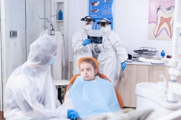 Medico dentista e assistente in possesso di radiografia dentale di un paziente bambino nel corso del coronavirus. stomatologo durante il covid19 che indossa una tuta in dpi facendo la procedura dei denti del bambino seduto sul chai