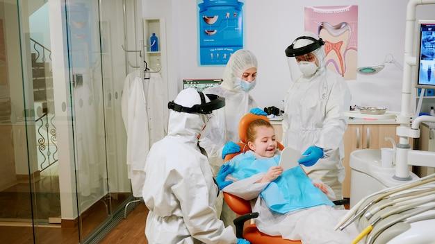 Medico dentista in tuta che termina il trattamento dentale del bambino in clinica stomatologica durante la pandemia globale. equipe medica che indossa tuta protettiva, maschera di protezione facciale e guanti che esaminano il paziente
