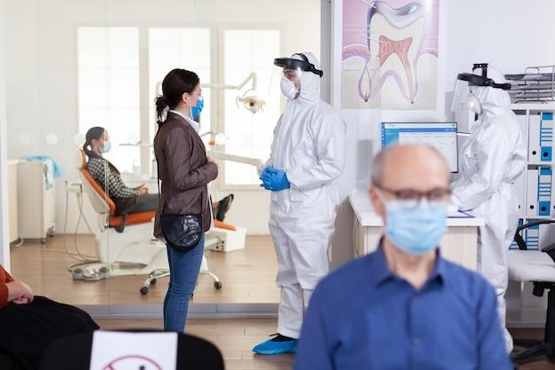 Medico dentista vestito con tuta in dpi che discute con il paziente nel corridoio di ricezione della stomatologia durante l'appuntamento, in tempo di pandemia globale con crisi sanitaria del coronavirus.
