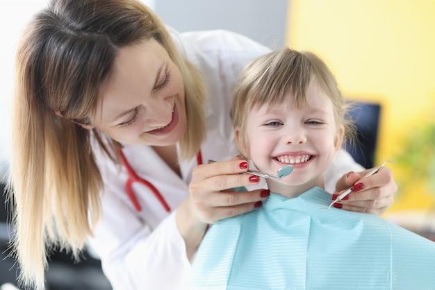 Il medico del dentista esamina i denti della bambina