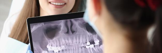 Il medico dentista esamina l'immagine a raggi x sullo schermo del tablet sulla sedia è una paziente donna