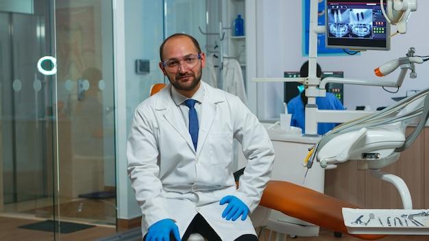 Medico dentista che guarda l'obbiettivo parlando con i pazienti di igiene dentale. stomatologo che parla in webcam seduto su una sedia in clinica stomatologica con assistente in background che lavora al computer