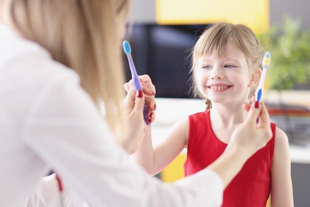 Medico dentista che offre alla bambina due spazzolini da denti tra cui scegliere in clinica