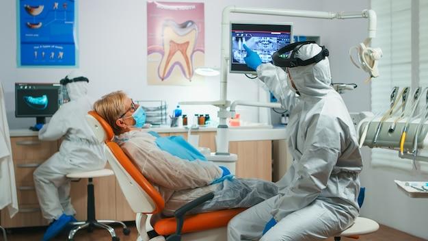 Medico dentista in tuta protettiva che spiega al paziente anziano il processo di chirurgia dentale durante la pandemia di covid-19. infermiera e ortodontista che indossa una tuta con visiera, guanti con maschera prima dell'esame