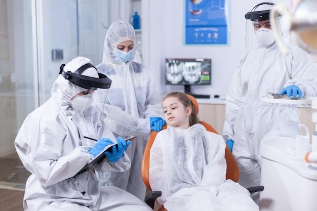 Medico dentista con maschera facciale e tuta che tiene appunti vestito con tuta stomatologo durante il covid19 che indossa tuta dpi facendo la procedura dei denti del bambino seduto sulla sedia.