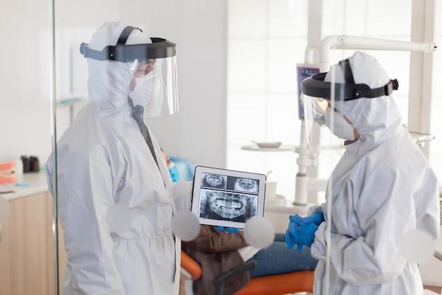 Medici dentisti con tuta in dpi che analizzano i raggi x dei denti utilizzando tablet nella stanza dentale, pianificando un intervento chirurgico durante la pandemia globale mentre il paziente aspetta sulla sedia stomatologica