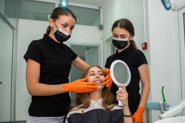 Il dentista esamina il paziente con le parentesi graffe. assistenza sanitaria