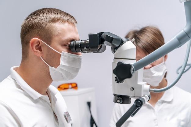 Il dentista esamina i denti del paziente con un microscopio dentale.