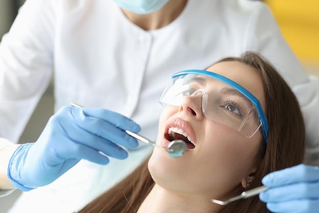 Il dentista esamina la cavità orale della donna in primo piano dell'ufficio