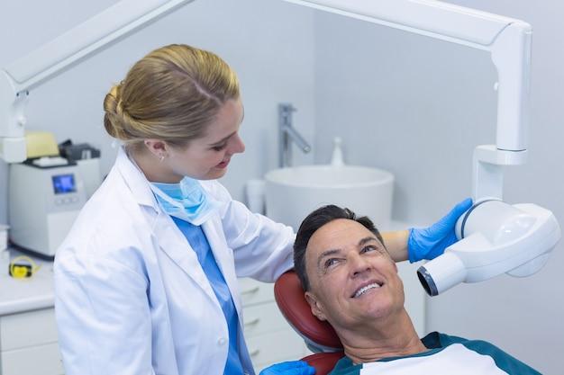 Dentista che esamina un paziente maschio con lo strumento dentale