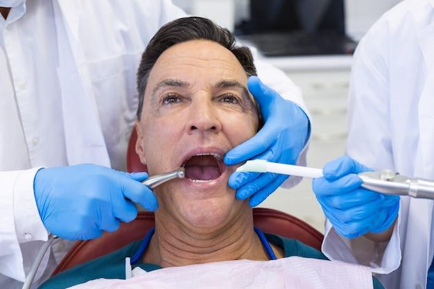 Dentista che esamina un paziente maschio con gli strumenti