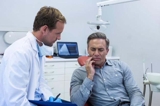 Dentista che esamina un paziente maschio