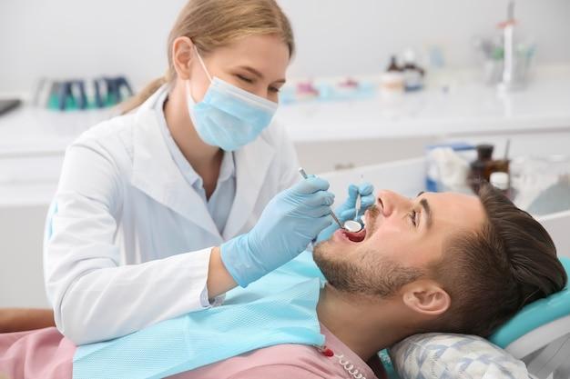 Dentista esaminando i denti del paziente in clinica