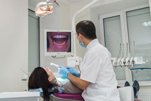 Dentista che esamina i denti del paziente con telecamera intraorale