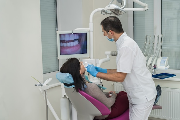 Dentista che esamina i denti del paziente con la telecamera intraorale