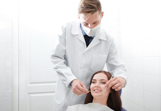Dentista che esamina i denti del paziente in clinica