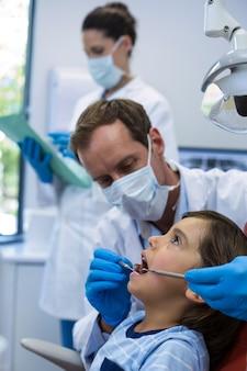 Dentista che esamina un giovane paziente con gli strumenti