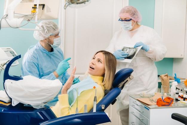 Il dentista spiega i dettagli della radiografia al collega, il paziente è sorpreso da ciò che sta accadendo.