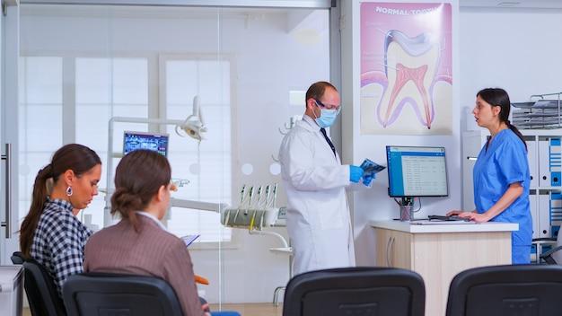 Dentista che finisce con il vecchio, chiedendo all'infermiera la prossima radiografia dentale durante l'attesa dei pazienti. ortodontista e infermiere che lavorano in una moderna clinica stomatologica affollata, stomatologo che guarda i raggi x