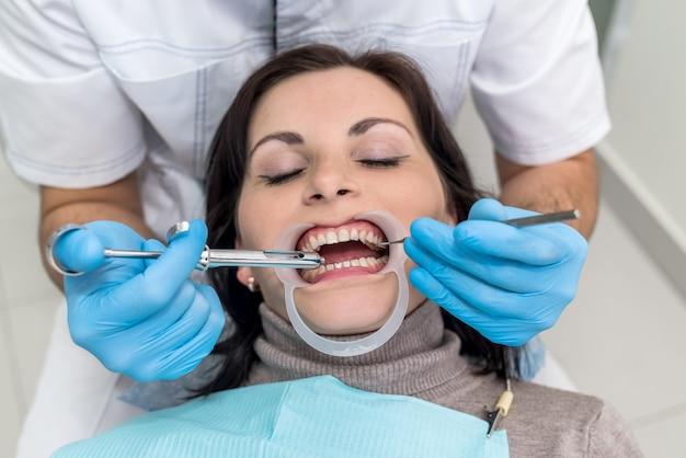 Mani del dentista con strumenti e primo piano del viso del paziente