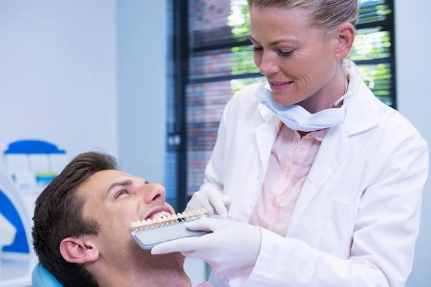 Dentista che tiene attrezzatura durante l'esame del paziente presso la clinica medica