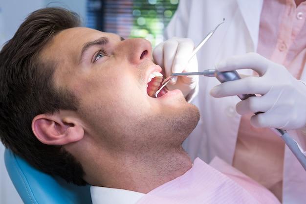 Dentista che tiene attrezzatura medica mentre dà il trattamento al paziente alla clinica