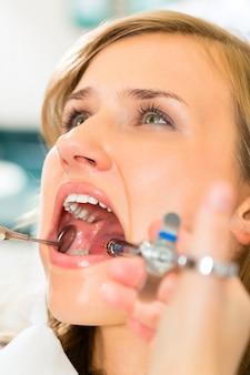 Dentista in possesso di una siringa e anestetizzando il suo paziente