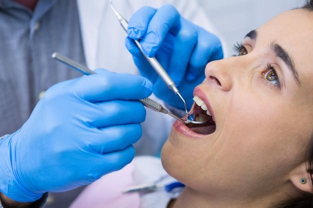Dentista che tiene gli strumenti mentre esamina la donna alla clinica