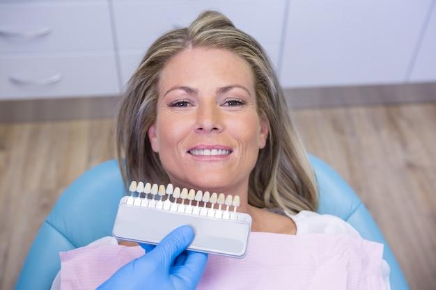 Dentista che tiene i denti che imbiancano attrezzature sorridendo paziente alla clinica