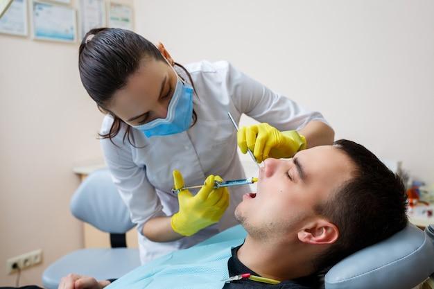 Il dentista inietta il paziente nella gengiva per anestetizzare i denti. trattamento del cavo orale. cure odontoiatriche. foto di alta qualità