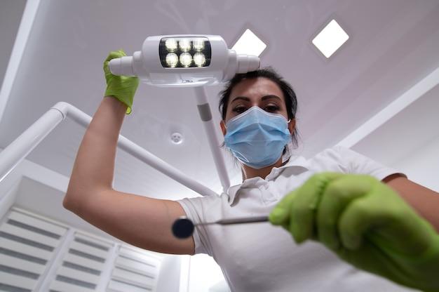 Dentista guardando verso il basso con specchio dentale in mano durante la regolazione della lampada in ufficio