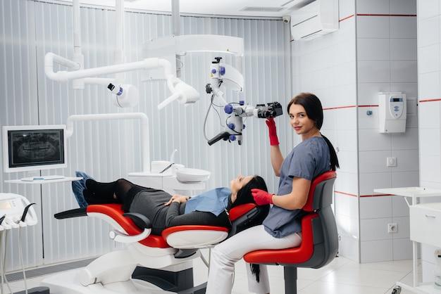 Il dentista guarda al microscopio ed esegue un intervento chirurgico sul paziente.